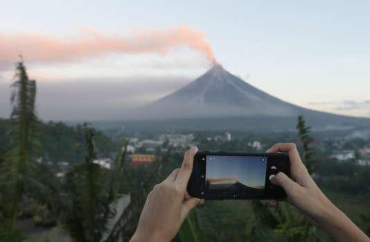 Un habitant prend une photo du Mayon le 23 janvier 2018, depuis la ville voisine de Legazpi, alors que ce dernier entre en éruption.