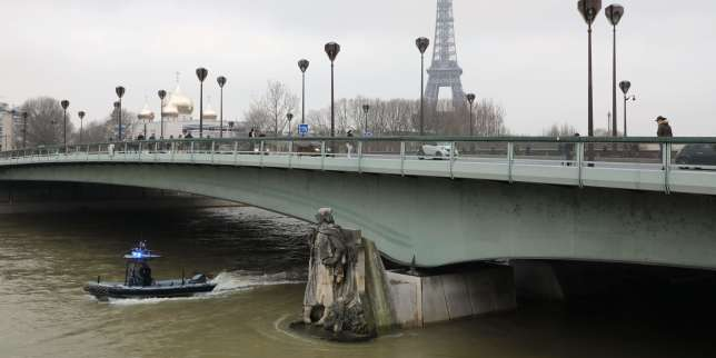 A waterway police boat patrols on the waters of the river Seine whose level has risen near the statue of the Zouave at the Alma bridge in Paris. / AFP / ludovic MARIN