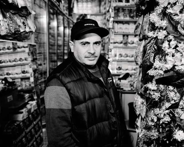 Lahoussine Abalhaoune sur le seuil de sa supérette, à Paris, dans le IXearrondissement. Arrivé en 1983 du Maroc, il observe impuissant l'érosion de son chiffre d'affaires.