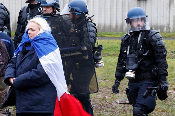 Une gardienne de prison porte un drapeau français alors qu'elle se tient près des gendarmes devant la prison de Maubeuge lors d'une manifestation nationale, le 24 janvier.