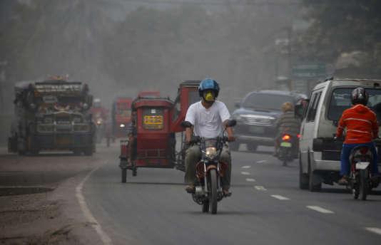 Les automobilistes utilisent des masques pour se protéger des cendres volcaniques tombées sur la ville de Guinobatan, le 24 janvier 2018.