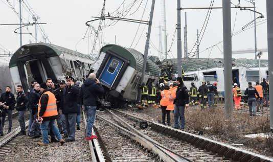 Des officiers de secours et de police se tiennent près du train qui a déraillé à Pioltello, dans la banlieu de Milan, le25janvier2018.