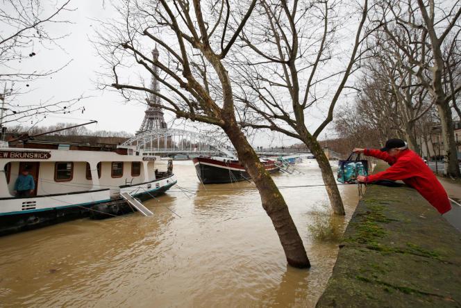Un homme transfère un sac, à l'aide d'une corde, à un ami vivant sur une péniche sur la Seine en crue, le 25 janvier.
