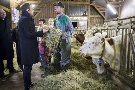 Emmanuel Macron avec Stéphane Travert, ministre de l'agriculture (à gauche), lors de sa visite du GAEC des Violettes, à Aurières (Puy-de-Dôme), le 25 janvier.