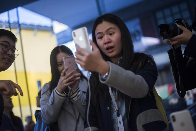 Une jeune femme teste la reconnaissance faciale de son iPhone X dans un magasin Apple à Pékin, le 3 novembre 2017.