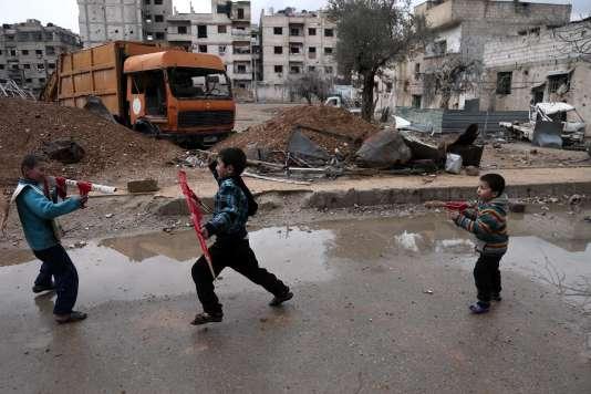 Des enfants jouent à la guerre dans la banlieue est de Damas, à Harasta, le 25 janvier.