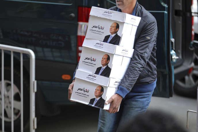 """«Avec ce scrutin présidentiel qui ressemble à un plébiscite, le président égyptien Abdel Fattah al-Sissi assume le vrai visage de son pouvoir, dans la lignée des autocrates égyptiens qui l'ont précédé avant la parenthèse qu'a été la révolution du 25 janvier 2011». (Photo sortie sur le compte officiel Facebook du président égyptien où l'on voit un homme portant des affiches électorales avec le portrait d'Abdel Fattah al-Sissi et le slogan """"Longue vie à l'Egypte"""")."""