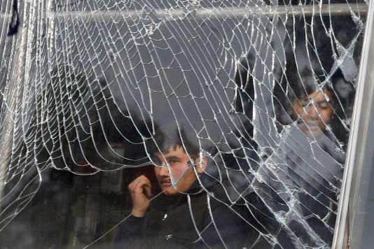 Un boutiquier derrière la vitrine cassée de son échoppe, à Kaboul, le 27 janvier.