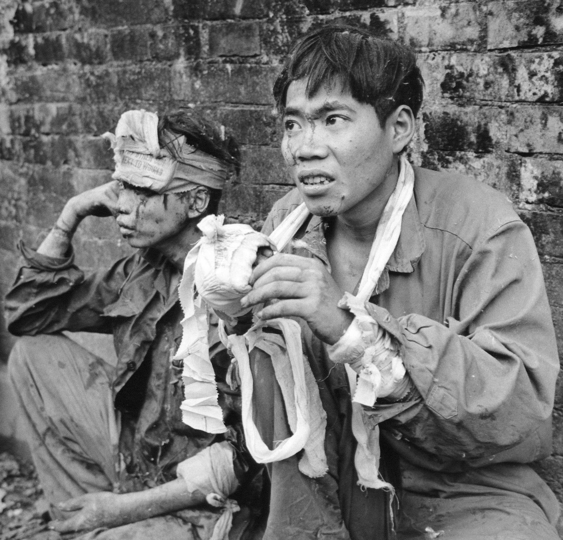 Deux prisonniers communistes attendent d'être transférés dans un centre d'interrogatoire, dans la citadelle de Hué, le 27 février 1968.
