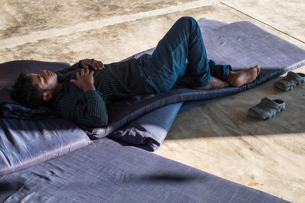 Danis, 19 ans, est originaire du Honduras. Il se repose, le26janvier2018, après plusieurs jours de marche, chaussé de simples sabots en plastique, pour rejoindre la Maison des migrants d'Arriaga, dans le sud du Mexique.