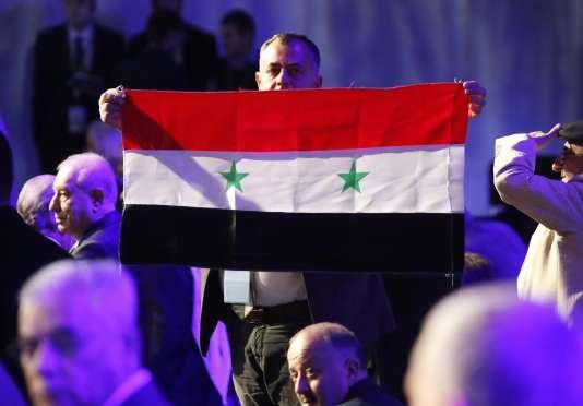 Un participant au Congrès pour la paix en Syrie brandit un drapeau officiel syrien, le 30janvier à Sotchi, en Russie.