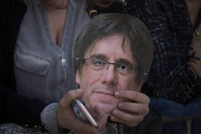 Une militante indépendantiste arbore un masque représentant l'ancien président régional Carles Puigdemont lors d'une manifestation devant le Parlement régional à Barcelone, en Espagne, le 30 janvier.