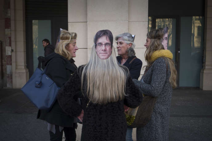 Manifestantes en faveur du président en exil Carles Puigdemont portent un masque à son effigie devant le Parlement catalan, à Barcelone, le 30 janvier.