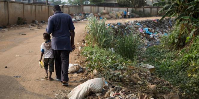 Moustapha Sangaré, ancien travailleur à la décharge d'Akouédo et son fils, au bord du caniveau où a été déversée une partie des déchets.