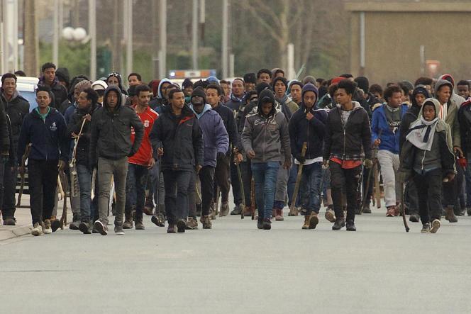 Des migrants munis de bâtons marchent dans les rues de Calais, le 1er février.