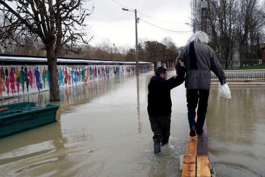 Un employé municipal aide un habitant de Gournay-sur-Marne (Seine-Saint-Denis), le2février.