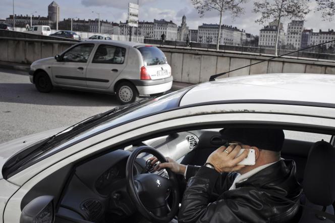 Un homme téléphone au volant de sa voiture, en 2012 à Lyon.