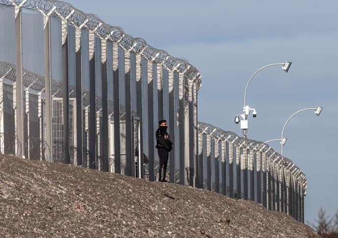 Un policier français devant une clôture le long de l'A16 à Coquelles, près de Calais (Pas-de-Calais), en janvier 2016.