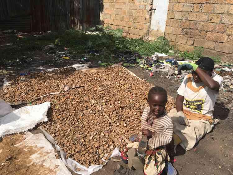 Assise en plein soleil au côté de sa fille, Isabella trie des capsules de bouteille. « C'est un travail difficile, mais je dois gagner de l'argent », dit Isabella. Le kilo de capsules lui rapporte 3 shillings (moins de 3centimes d'euros).