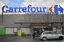 A woman leaves a French retail giant Carrefour supermarket in Nantes, on January 26, 2018.  France's Carrefour group said on January 23, 2018 it is overhauling its business in a transformation plan involving thousands of job cuts, a product revamp and new partnerships in China.   / AFP PHOTO / LOIC VENANCE