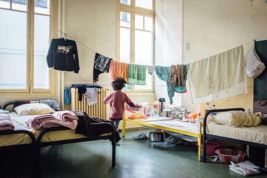 Un enfant afghan joue dans la salle de classe aménagée en chambre qu'il partage avec sa famille.