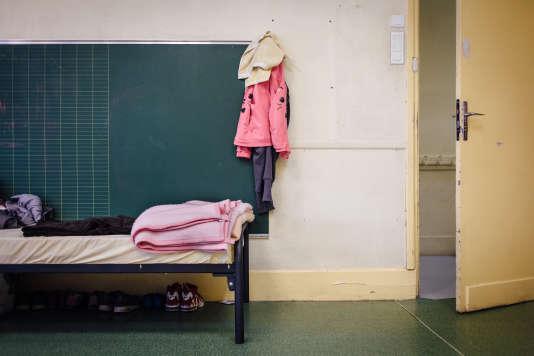 Dans une salle de classe aménagée en chambre, occupée par une famille d'origine afghane.