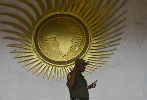 A security personnel stands by a sculpture representing the African continent, before the start of the 30th Ordinary Session of the Assembly of Heads of State and Government of the African Union (AU), in the entrance hall of the AU headquarters in Addis Ababa on January 27, 2018. / AFP PHOTO / SIMON MAINA