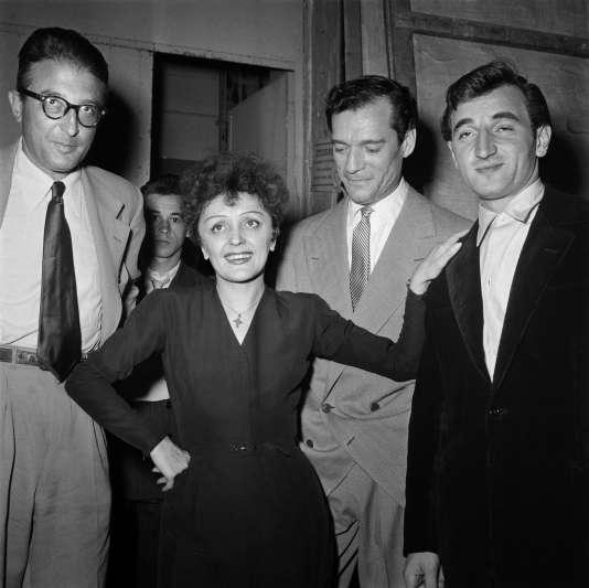 Edith Piaf pose avec le compositeur français Michel Emer (à gauche), l'acteur américain Eddie Constantine (2e droite) et Charles Aznavour (à droite), en 1950, à Paris.
