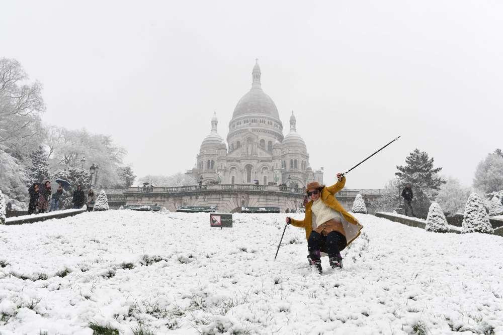 Une femme skie sur la colline de Montmartre enneigée devant la basilique du Sacré-Cœur, le 6 février à Paris.