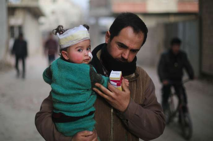 Un homme porte un bébé blessé à la suite des bombardements à Arbin dans l'enclave de la Ghouta orientale, près de Damas, le 8 février.