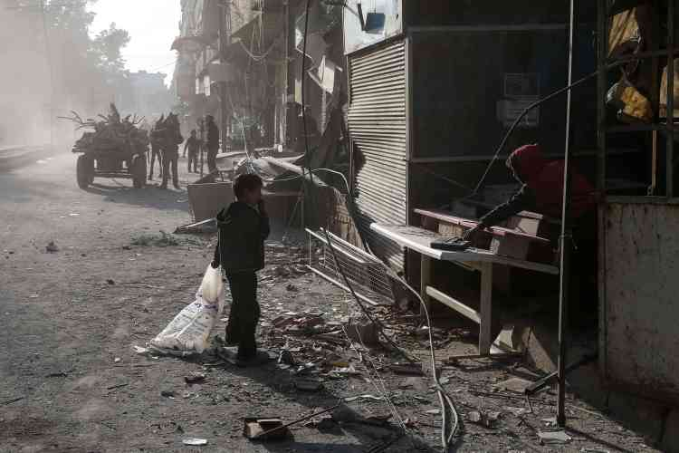 Des enfants nettoient une échoppe des débris projetés par un bombardement, à Kafr Batna, le 6 février.