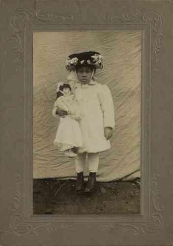 «C'est là un très beau portrait. Sur la toile tendue pour servir de fond, cette petite fille semble bien avoir été missionnée pour figurer toute l'élégance et la respectabilité des femmes africaines-américaines, à l'époque duNew Negroet de la Harlem Renaissance (dans les années 1920). Pas certain qu'elle goûte particulièrement la pose – mais elle serre fort dans ses bras ce qui peut bien être sa poupée préférée, tout en étant un symbole social : une poupée blanche toute en robe et porcelaine. »