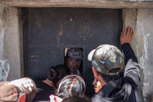 Les familles de migrants attendent leurs proches face à une porte de l'aéroport militaire où arrive les migrants Guatémaltèques expulsés des Etats-Unis.