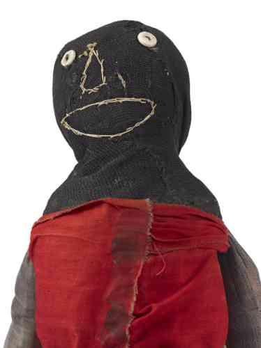 """«Variation autour de la """"sock-doll"""" : cette poupée-chaussette légère et rembourrée rend manifeste l'originalité et l'inventivité de la vision de son auteure, mais aussi, peut-être, ses transformations successives par ses propriétaires: la peinture, désormais délavée, de """"boutons"""" sur sa chemise rouge est sans doute postérieure à la broderie de fil blanc qui figure les traits du visage. »"""