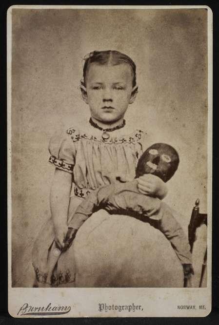 """«Le style de la poupée ici représentée diffère grandement des poupées de la collection Neff ; on suppose qu'elle a été faite par une personne blanche, vision stéréotypique des Noires que vient confirmer la légende de la photographie: """"Mary Jones and Dinah"""", ce prénom étant le cliché onomastique de la servante noire. La ressemblance de la poupée avec un masque est redoublée par le masque du visage de la fillette (dont on reconnaît le sexe non pas à la robe, qui pouvait être unisexe, mais à la raie au milieu), qui s'affranchit quelque peu des canons de la joliesse de l'époque. »"""