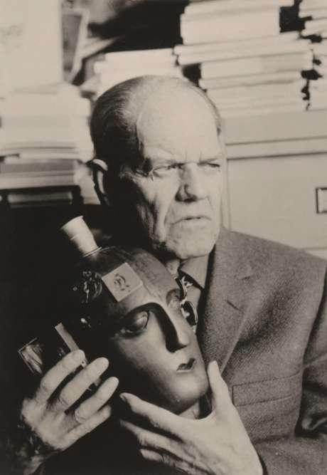 """« En quittant précipitamment l'Allemagne peu après la prise de pouvoir nazie en 1933, Hausmann laissa ses œuvres dadas à l'artiste Hannah Höch, son ancienne compagne. Celle-ci les sauva de la destruction en les enterrant dans son jardin, la nuit, sans s'éclairer, ce qui attira l'attention des voisins ; mais quand les nazis vinrent la questionner, ils ne trouvèrent rien. Hausmann ne put récupérer sa """"Tête"""" qu'en1967. Cette photographie est celle de ses retrouvailles avec cet objet dont il fut si longtemps privé. »"""
