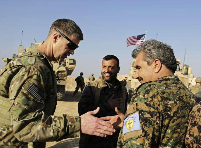 Un général américain (à gauche) serre la main d'un commandant des Forces démocratiques syriennes, à Manbij, le 7 février.