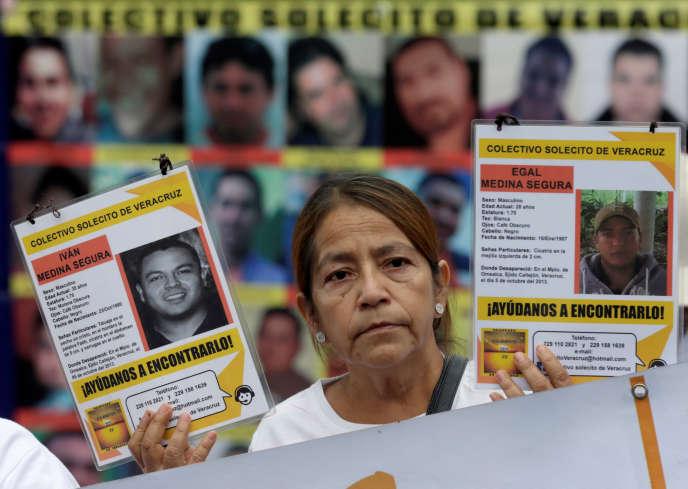 Une femme tenant les photos de membres de sa famille ayant disparu.
