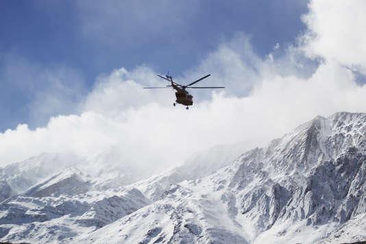Un helicoptère survole les monts Zargos, en direction du mont Dena au lendemain d'un crash d'avion survenu le 18 février.