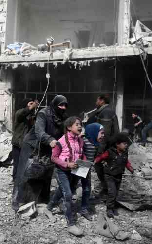 Des habitants de la ville rebelle d'Hamouria cherchent un abri parmi les décombres, le 19février.