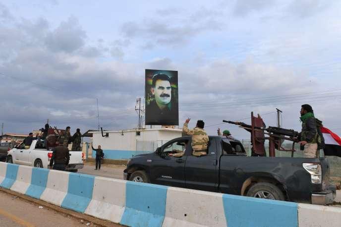 Un convoi de combattants pro-Assad passe devant un portrait du leader du Parti des travailleurs du Kurdistan (PKK) Abdullah Öcalan, à son arrivée dans la région d'Afrin, dans le nord de la Syrie.