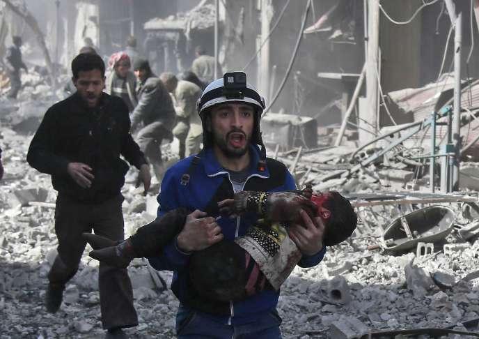 Un Casque blanc transporte un enfant blessé suite aux bombardements de l'armée syrienne à Hamouria, à l'est de Ghouta (syrie), le 19 février.