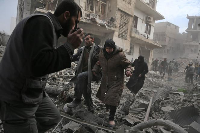 Un membre des casques blancs syriens aide à évacuer des civils après le bombardement d'un immeuble dans le quartier de Saqba dans la Ghouta orientale, le 20 février.