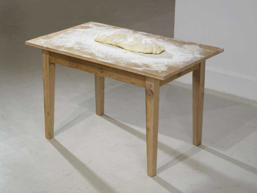 """« Apremière vue """"Atta"""" (2010), ne semble être qu'un peu de pâte à pain enfarinée sur une rudimentaire table en bois. Subodh Gupta, pourtant, se joue de nous, cachant le métal derrière le masque du quotidien. Placées au début de l'exposition, ces œuvres en trompe-l'œil sont à l'échelle de la main et contrastent avec """"Very Hungry God"""".»"""