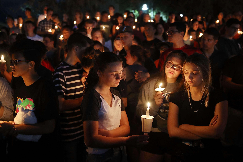 Lors d'une cérémonie d'hommages aux enseignants et lycéens tués, à Parkland, le 15février. Un tireur de 19ans a ouvert le feu, mercredi 14 février, dans le lycée Marjory-Stoneman-Douglas de Parkland, dans le sud-est de la Floride, faisant 17 morts.Le tireur, un ancien élève renvoyé de l'établissement pour des raisons disciplinaires a été arrêté non loin de l'école. Il s'est rendu sans résistance à la police. Il était armé d'un fusil d'assaut de type AR-15 et avait de très nombreuses munitions.