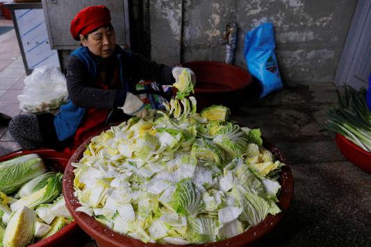 Une femme prépare le kimchi sur le marché de Gangneung.