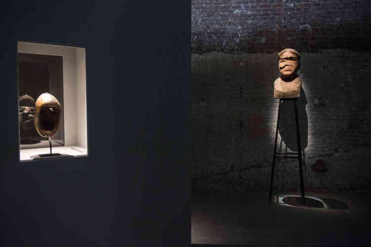 De face, l'une des «gueules cassées» sculptées dans le bois par Kader Attia ; de dos, l'un des masques de maladies africains de sa collection.