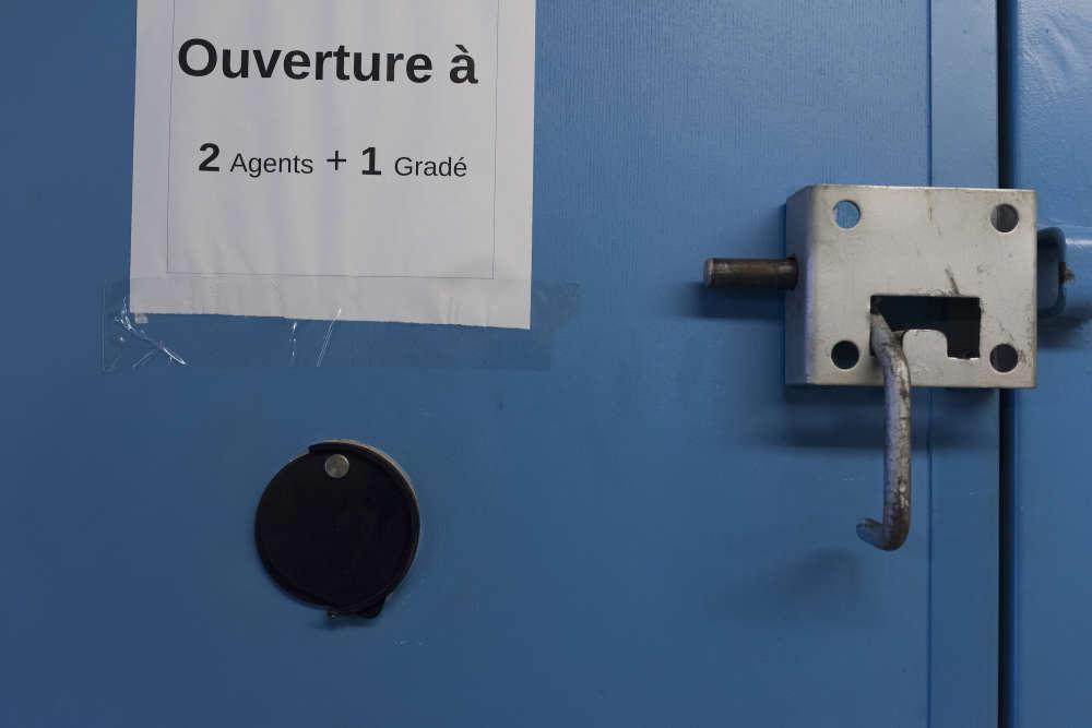 Fiche signalant la présence d'un détenu dangereux apposée à la porte de sa cellule. Il y est maintenu seul. L'« arme » dont disposent les surveillants en cas de pépin, c'est un sifflet pour donner l'alarme. Le gradé possède en plus une paire de menottes.