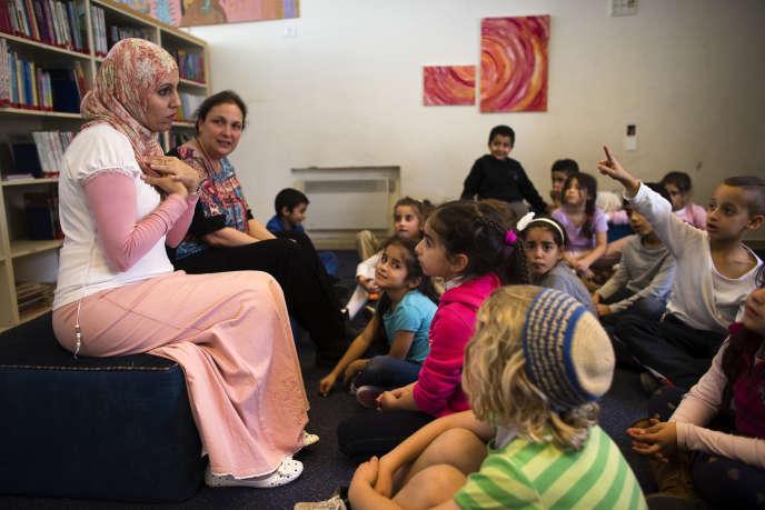 Des enseignants de première année parlent à leurs élèves pendant l'heure de lecture à l'école bilingue juive arabe de Hand in Hand, à Jérusalem, en décembre 2014.