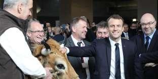 Emmanuel Macron caresse une vache aubrac au 55e Salon de l'agriculture, sorte de «village Potemkine», installé à Paris du 24 février au 4 mars.